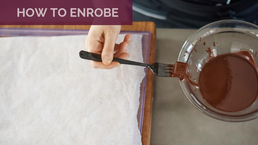 Dipping a praline into chocolate and sweeping off excess chocolate on the edge of the bowl